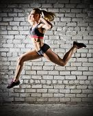 Muscular jumping woman on grey brick wall background (dark version)