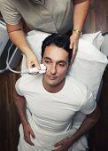 Handsome man having facial laser rejuvenation procedure