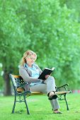 Mature lady reading a novel seated on a bench in park