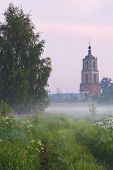 Old belltower early in the morning in fog
