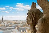 stock photo of gargoyles  - Gargoyle on Notre Dame Cathedral and city of  Paris close up - JPG