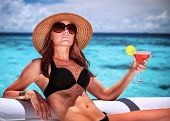 Portrait of sexy gorgeous female relaxing on luxury beach resort, sitting on lounger and drinking co