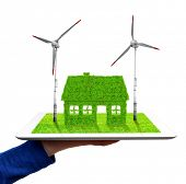 hand holding a tablet with green house and wind turbines
