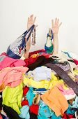 foto of untidiness  - Man buried under an untidy cluttered woman wardrobe - JPG
