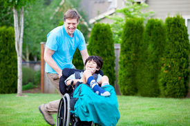 stock photo of wheelchair  - Father running with disabled son in wheelchair - JPG