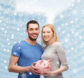 finance, money, people and family concept - smiling couple holding big piggy bank over snowy city center background