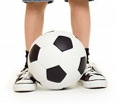 feet shod in sneakers and soccer ball studio isolated