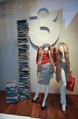 Boutique shop window with dressed mannequins and high pile of books