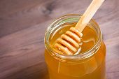 Honey Jar On Wood Table With Wooden Dipper On Top