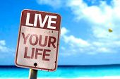Live Your Life sign with a beach on background