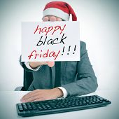 a man with a santa hat in an office desk showing a signboard with the text happy black friday written in it