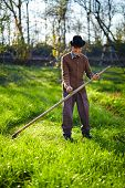 foto of scythe  - Senior farmer mowing the lawn with a scythe traditionally - JPG