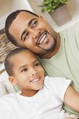 A happy African American man and boy, father and son, family sitting together at home