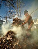 foto of fallen  - Senior farmer cleaning his garden of fallen leaves burning them in a pile - JPG