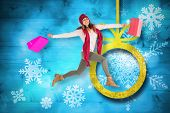 Smiling brunette jumping with gifts bags against christmas decorations over wood