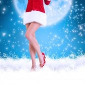 Lower half of sexy santa girl against blue background with vignette