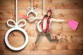 Happy brunette jumping with gifts bags against christmas decorations over wood