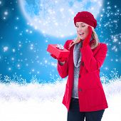Festive blonde holding red gift against blue background with vignette