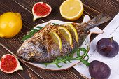 Whole grilled fish dorado served with lemon and figs