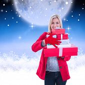 Festive blonde holding many gifts against white clouds under blue sky