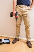 Construction worker holding power tool in a new house