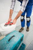 Plumber putting his tools on toilet in the bathroom