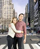 Young couple hugging on a cross walk on fifth avenue in New York