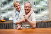 Senior couple smiling at the camera together at home in the kitchen