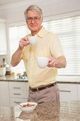Senior man offering cup to camera at home in the kitchen