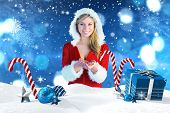 Pretty girl holding hands out in santa outfit against christmas scene with gifts and candy canes