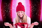 Pretty blonde opening gift bag against glittering screen on black background
