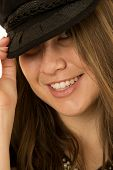 Close-up Of A Woman Peering Playfully Wearing Black Hat