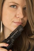 Protrait Of A Brunette Woman Peering Over A Black Gun