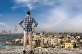 Asian man standing and looking the skyline of the city, Kaohsiung, Taiwan, Asia.