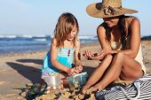 Mother and daughter looking at shell collection together interacting at the beach on weekend leisure fun