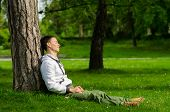 Happy Young Man Relaxing In The Park On Sunny Spring Day