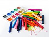 Watercolours And Heap Of Colourfull Crayons On White Background