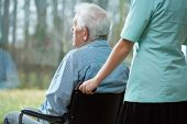 foto of handicapped  - Nurse and handicapped man looking from the window