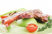 meat food : grilled beef spare rib on green dish with thyme pepper and tomato isolated over white background . shallow dof