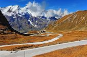 The well-known picturesque specific road in the Austrian Alps - Grossglocknershtrasse. Idealnoye Highway curls highly in mountains. The highest mountain tops are covered with fresh snow