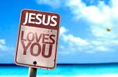 Jesus Loves You sign with a beach on background