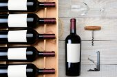 High angle shot of a case of red wine bottles with blank labels next to a single bottle a wineglass and cork screws on a rustic white wood table. Horizontal format.