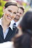 Portrait of a beautiful smiling young business woman or businesswoman with colleagues in team meeting outside