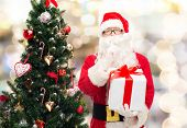 christmas, holidays and people concept - man in costume of santa claus with gift box and tree making hush gesture over lights background