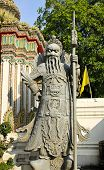 Ancient Statue In The Complex Of Wat Pho, The Temple Of The Reclining Buddha In Bangkok, Thailand.