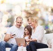 family, holidays, shopping, technology and people - smiling mother, father and little girl with tablet pc computer and credit card over lights background