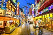 OSAKA, JAPAN - NOVEMBER 17, 2012: Crowds pass through Shinsekai district of Osaka. The area is a famed nightlife area.