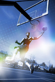 stock photo of slam  - A basketball player drives to the hoop for a slam dunk with abstract rainbow lens flare and halftone effects - JPG