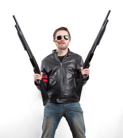 stock photo of shotgun  - Man in black leather jacket and sunglasses with two shotguns - JPG