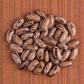 picture of pinto bean  - Top view of circle of pinto beans against red vinyl background - JPG